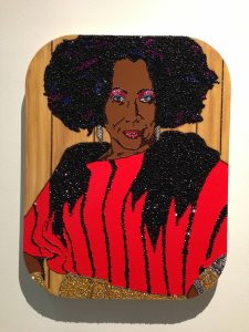 "Installation view of part of Mickalene Thomas's depiction of her mother: ""Ain't I Woman, Sandra,"" 2009. Rhinestones, acrylic paint, and oil enamel on wood panel. DVD and framed monitor; rhinestones, acrylic paint, and enamel on wood."