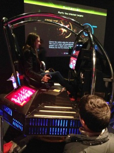 Child waits turn as museum-goer enjoys Galaxy Force II, Sega's 1988 arcade game built upon a flight-simulator cabinet.