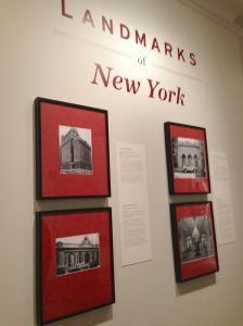 Installation view featuring photos of the Whitehall Building (17 Battery Place), Grand Central Terminal, the Free Public Baths (538 East 11th), and the interior of the Plaza Hotel