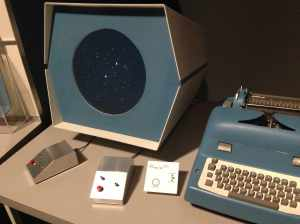 Replica of the round CRT and game controllers developed at MIT in 1962 to run Spacewar on DEC's PDP-1, the first commercial interactive computer. Note input-output typewriter.