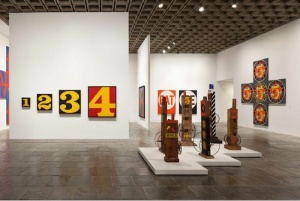 Scrounged wood assemblages hold court with Indiana's numbers and cruciform arrangement of Demuth-inspired canvases. © 2013 Morgan Art Foundation, ARS, NY Photo: Sheldan C. Collins