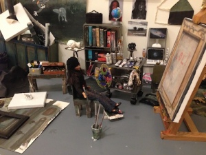 Close-up of the doll-artist contemplating her studio output in Julia San Martin's Dollhouse