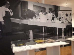 Notebooks and menu drawings from ElBulli's kitchen displayed in front of a mural of Ferran Adrià and staff in Roses, Spain in the most famous kitchen in the world. Courtesy: elBullifoundation, The Drawing Center