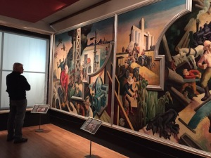 "Viewer contemplates ""The Changing West"" panel of Thomas Hart Benton's America Today mural (1930-1931)"