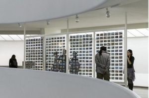Viewers peruse a fraction of the 1,800 postcards that On Kawara sent to document the time he got up at various cities in his travels. Photo by David Heald