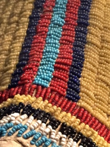 Close up of the tiny Venetian seed beads used to decorate a Lakota woman's dress (Teton Sioux), 1865. From the Smithsonian's NMAI
