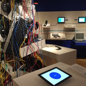 Tower of keyboards and wires in the center of the fourth-floor gallery; Newton visible against the history wall